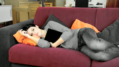 stock-footage-woman-sleeping-on-couch-hugging-tablet-dreaming-of-technology